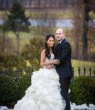 Bride in a strapless Lazaro dress with lace bodice, ruffled skirt & groom in black tuxedo