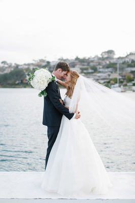 Bride in white wedding dress and groom in tuxedo embrace on pier in San Diego