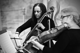 Black and white photo of a cellist and violinist from the Chicago Sinfonietta at wedding ceremony