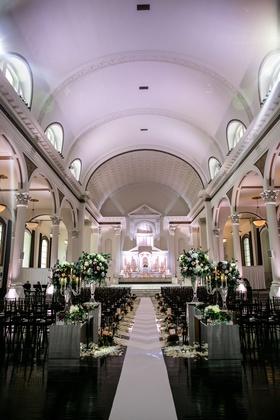 Vibiana wedding ceremony with white aisle runner greenery and burgundy flower arrangements altar