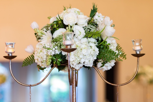 Wedding reception centerpiece with white hydrangeas, roses, tulips, verdure on copper candelabra