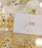 Wedding reception table with gold sequined runner, votive candles, white roses, and Zeus table name