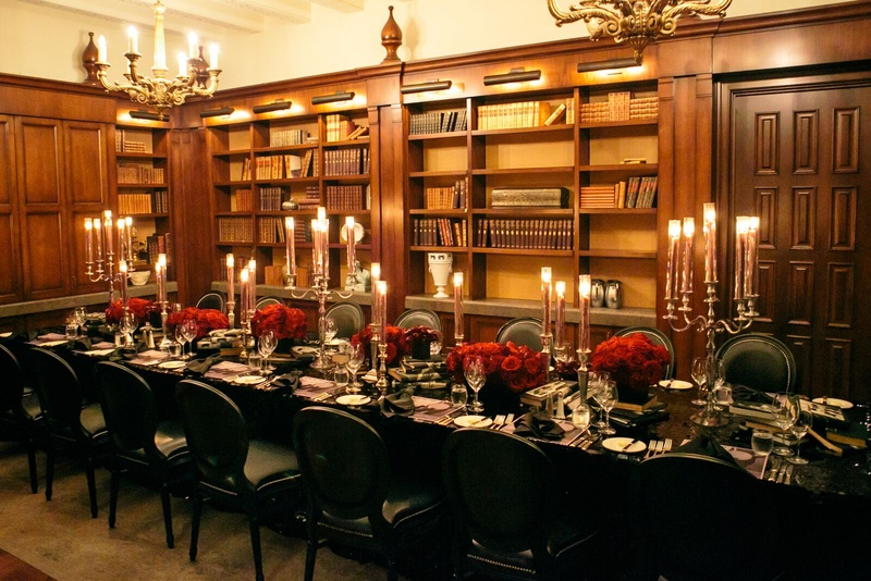 Stacked books, crimson flowers and moody candlesticks dressed up this table set in an antique librar