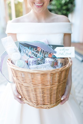 Bride in off shoulder wedding dress white manicure holding welcome basket with goodies