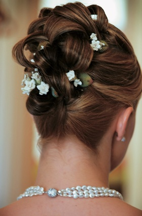 Braided updo hairstyle studded with tiny flowers