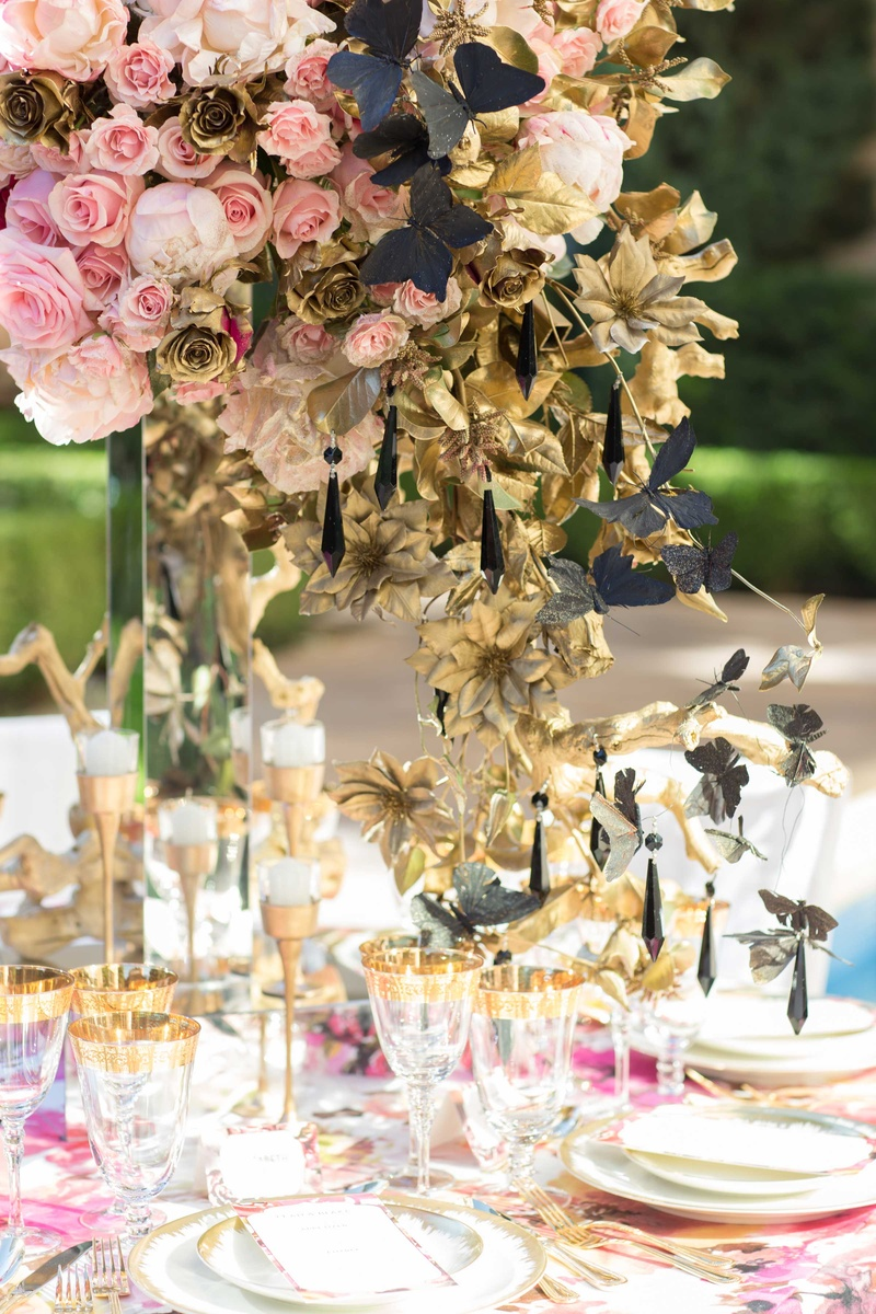 large overflowing floral centerpiece with floral linens and gold details on plates and glasses