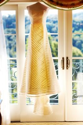 Anne Barge stripe wedding dress hanging in front of door