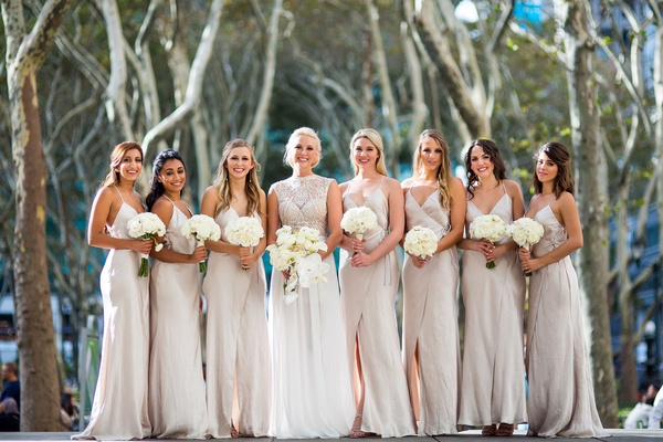 Bride in julie vino wedding dress with orchid bouquet and bridesmaids in spaghetti strap wrap gowns