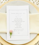 Bridal shower place setting with golden charger, cream napkin, white menu, tiny rosebud