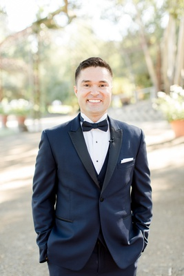 smiling groom in midnight blue tuxedo with his hands in his pockets
