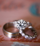 Solitaire diamond engagement ring with diamonds on setting and men's wedding band with rose gold