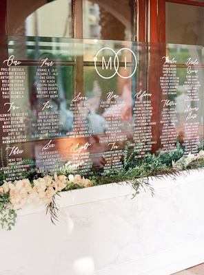 acrylic sheet with wedding seating chart in bed of orchids and greenery