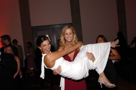Bridesmaid in red dress holds bride at wedding reception