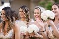 bridesmaids in mismatched gold sequin gowns smiling and happy to see the bride and groom