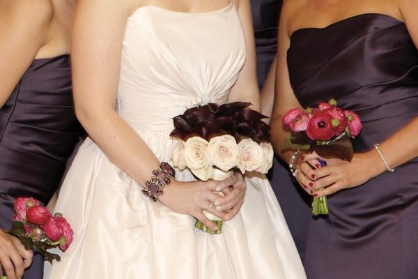 Bride's bouquet of maroon calla lilies and pink roses with bridesmaids' bouquets of fuchsia roses