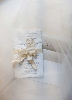 a couples white wedding invitation with cream ribbon tied around sits atop tulle