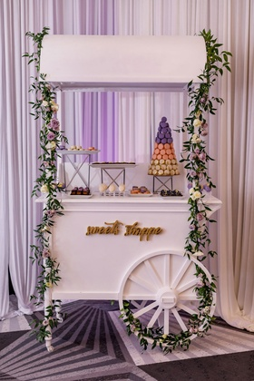 Wedding reception dessert cart idea macaron tower desserts on trays garland flowers
