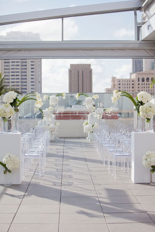 White outdoor wedding ceremony with ghost chairs and calla lily flowers