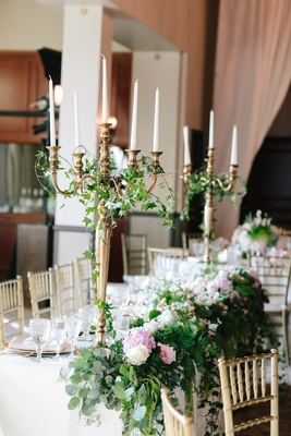 Tall gold candelabrum centerpieces with green ivy and pink white flowers with greenery