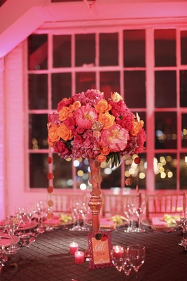 Gold centerpiece stand with pink and orange flowers
