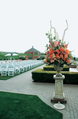 Outdoor wedding ceremony with stone urn full of orange and pink flowers