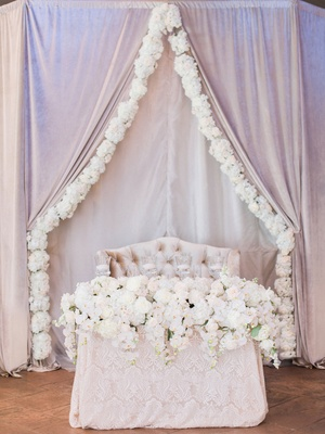 Wedding reception drapery with flower border over sweetheart table lace tablecloth with white flower