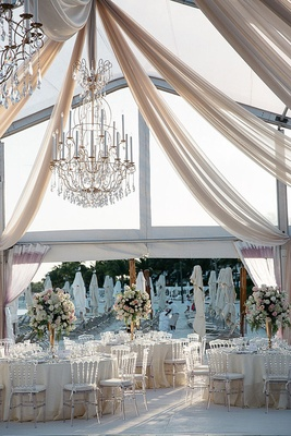 Beach wedding reception with a clear tent, drapery, and golden chandeliers with crystals
