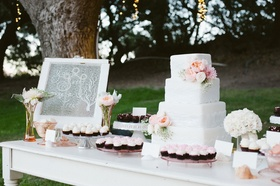 Pink cupcakes and white wedding cake with fresh flowers