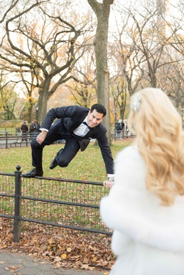 a groom in a black tuxedo jumps a fence in new yorks central park to get to bride