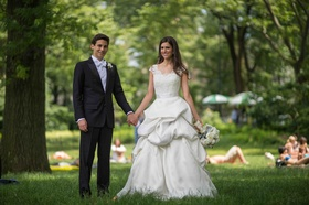 Bride in a Monique Lhuillier gown with a pick-up skirt and groom in a black tuxedo