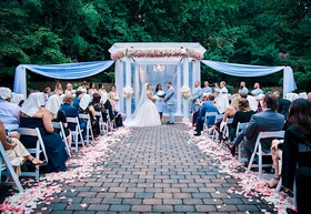wedding ceremony courtyard brick aisle white pink flower petals drapery arch arbor pink flowers