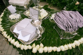Ceremony presentation table covered by green leaves, with a rim or white rosebuds