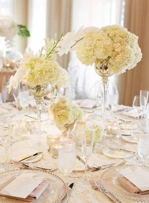 Round wedding table with rosette linen, mercury glass vessels with hydrangea and orchid flowers