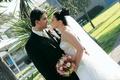 Newlyweds kiss on grass
