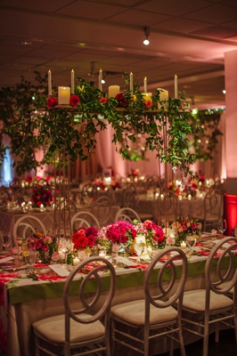 Wedding reception flower print table cloth with greenery candle display on thin stand over table