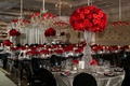 wedding reception ghost chairs black chairs red rose flowers crystal silver linens chandelier damask