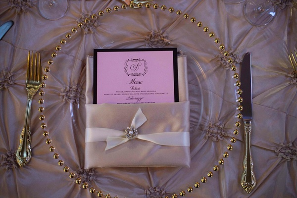 Wedding reception place setting with a clear charger with beaded golden rim and pink linens