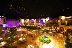 Wedding reception that looks like outdoor venue ballroom high ceilings balcony fountain trees lights