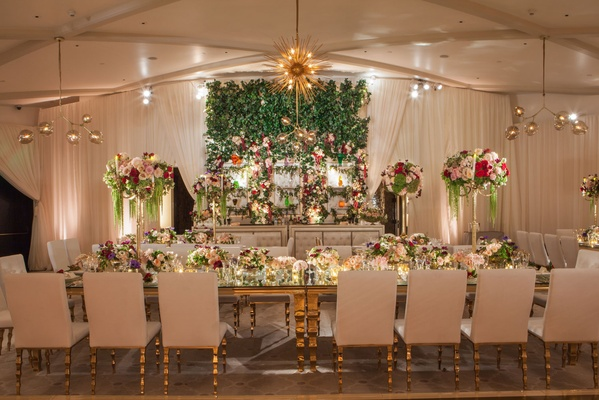 Wedding reception with white gold furniture and flowers in green red burgundy pink white flower wall