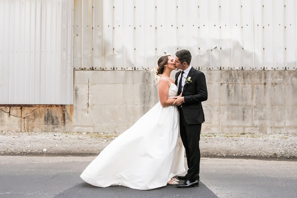 bride in modern trousseau ball gown with lace back, spaghetti straps, and pockets, kisses groom