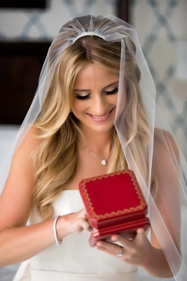 Bride in strapless wedding dress, bracelet, veil, necklace opening red jewelry box