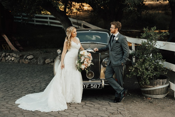 Bride and groom facing each other while leaning against a vintage rolls royce