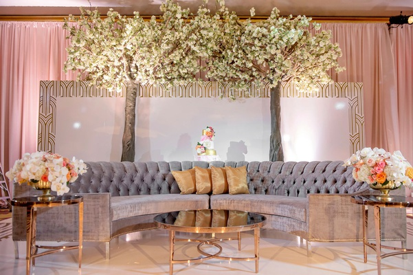 wedding reception flowered trees grey tufted semi circle sofa gold pillows coral pink flowers gold