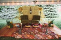Plush seating and mendhi ceremony items on colorful linens