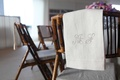 white table cover featuring silver initials embroidered onto cloth