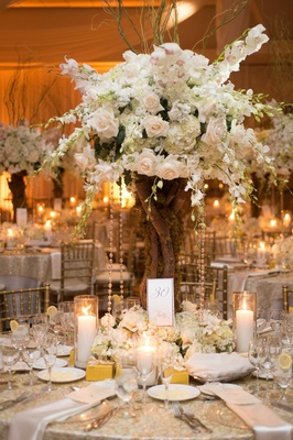 Indoor wedding reception with tree branch centerpiece