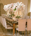 Mirror top wedding reception table with white chameleon chairs ruched and white pink centerpieces