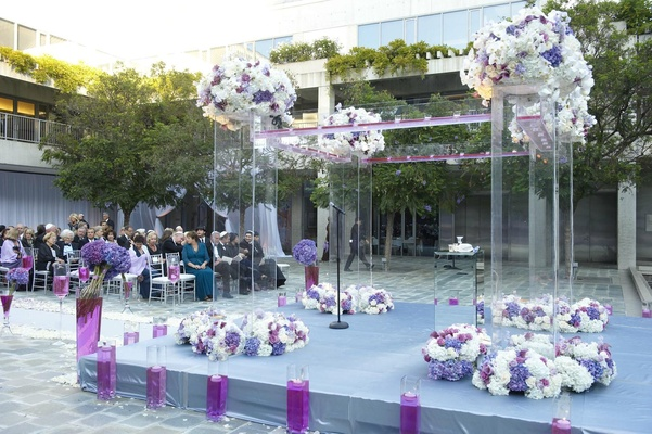 Clear chuppah with purple and white flowers at outdoor ceremony