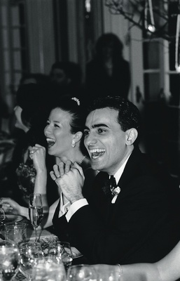 Black and white photo of couple laughing at reception