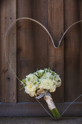 Bride's bouquet of white flowers with greenery, bound by white ribbon, against wood barn door